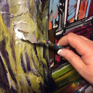 Theresa Eisenbarth working a palette knife in her art studio